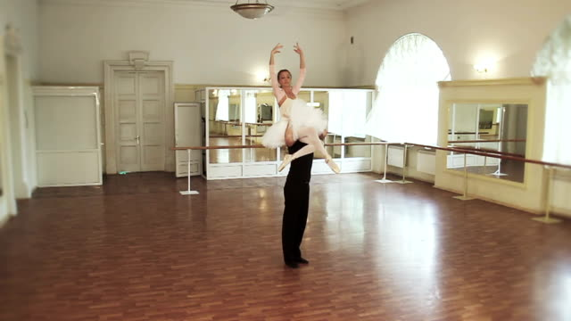 Male dancer lifts female onto his shoulders, ballet dancing video