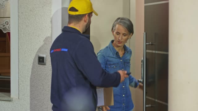 Male delivery service worker delivering a package to a woman