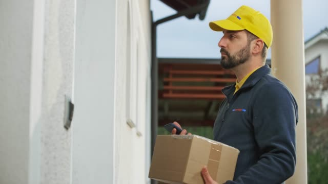 Male delivery service worker handing a package to the female customer at her home