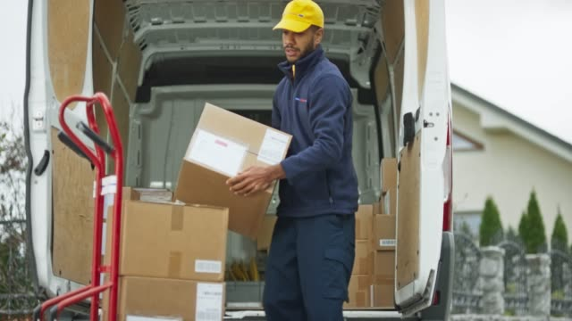 Male delivery service worker placing packages from the van onto the cart