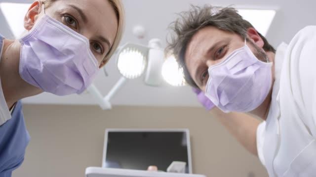 pov manliga tandläkare och hans assistent tittar på patienten på stolen - two dentists talking bildbanksvideor och videomaterial från bakom kulisserna