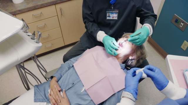 a male dentist wearing an n95 mask adjusts his dental light above a female patient in her sixties who removes her face masks as she lies in a dentist's chair in the examination room of a dental clinic as a dental hygienist assists - dentist стоковые видео и кадры b-roll