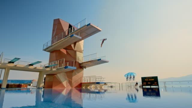 cs männlich taucher von der höchsten plattform in der ruhigen pool springen und drehen in der luft vor der landung im wasser - nackter oberkörper stock-videos und b-roll-filmmaterial