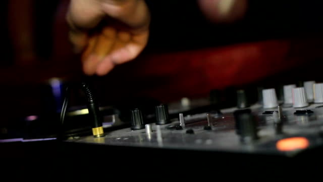 Male DJ Controls sound remote in night club video