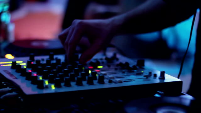 Male DJ mixing records, tweaking, pressing buttons, equipment video