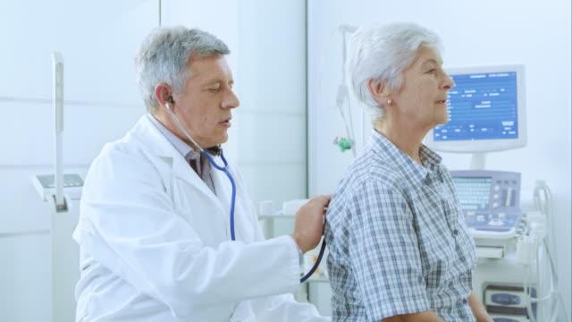 雄医師 auscultating 女性彼女の背中を患者の肺 - 聴診器点の映像素材/bロール