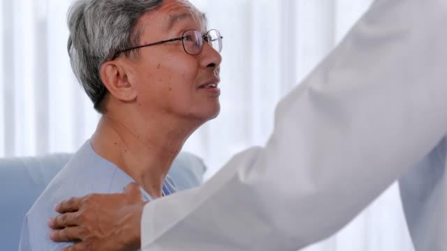 männlicher arzt tröstet patienten senior mann im beratungsraum. pflegearzt im krankenhaus im gespräch mit älteren mann im krankenhaus. medizin, alter, gesundheitswesen, kardiologie und menschenkonzept. gesundheitswesen: pflege - geduld stock-videos und b-roll-filmmaterial
