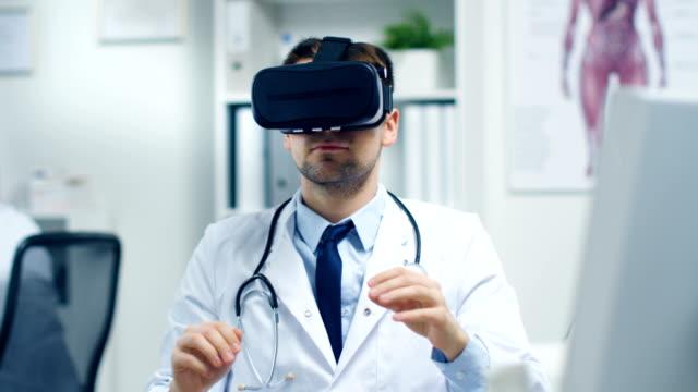 Macho médico realização de procedimento médico Experimental usando fone de realidade Virtual. Seu assistente estreitamente monitora a atividade da mesa dele. Moderno é leve e ultra moderno. - vídeo