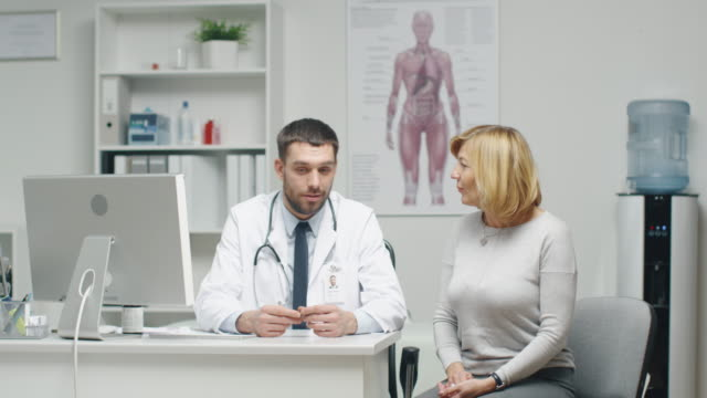 Male Doctor Consults Mid Adult Female Patient. They Talk and Smile.