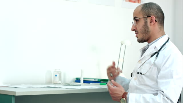 Male doctor describing diagnosis and showing bottle of pills to his patient video
