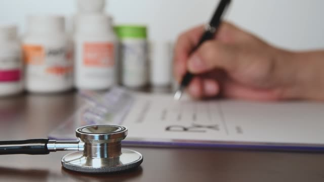 male doctor hands writing rx prescription. - prescrizione medica video stock e b–roll