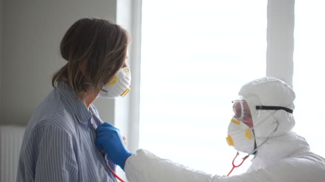 Video Male doctor in a protective suit listens to the breath of an elderly sick woman using a phonendoscope. Dangerous virus, symptoms of coronavirus