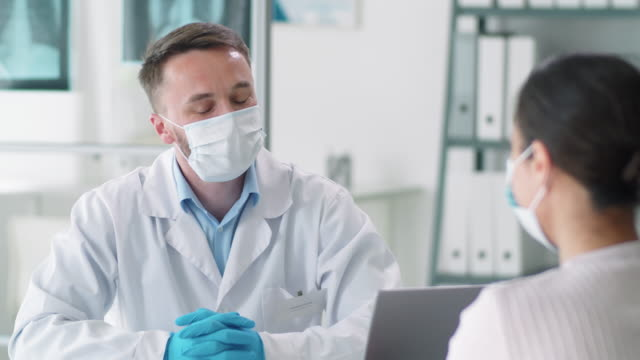 Male Doctor in Protective Mask and Gloves Talking to Woman in Medical Office