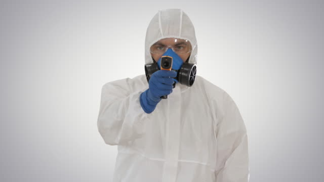 Male doctor in protective suit holding an digital infrared thermometer pointing with it to camera on gradient background