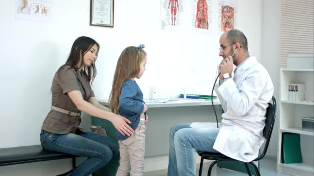 vídeos y material grabado en eventos de stock de doctor masculino escuchar niña tórax con estetoscopio en su oficina - pediatra
