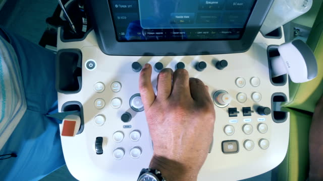 male doctor pushes buttons on a ultrasound device, top view. - медицинский рентген стоковые видео и кадры b-roll