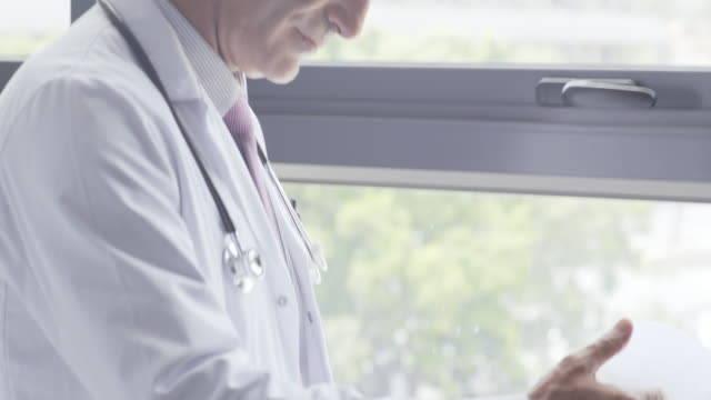 Male doctor reviewing medical chart by window Tilt up shot of male doctor reviewing medical chart in hospital. Mature medical professional is holding clipboard while looking through window. He is wearing lab coat. leaning stock videos & royalty-free footage