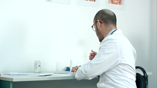 Male doctor shaking down thermometer and handing it to the patient video