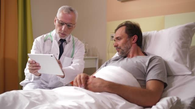 vídeos y material grabado en eventos de stock de médico masculino que muestra los resultados de la rmn al paciente - repuesto