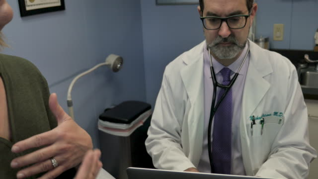 Male doctor taking medical notes on a laptop while a female patient talks Male doctor taking medical notes on a laptop while an female patient talks about her medical history or illness during a doctor's visit - dolly shot tilt up ignoring stock videos & royalty-free footage