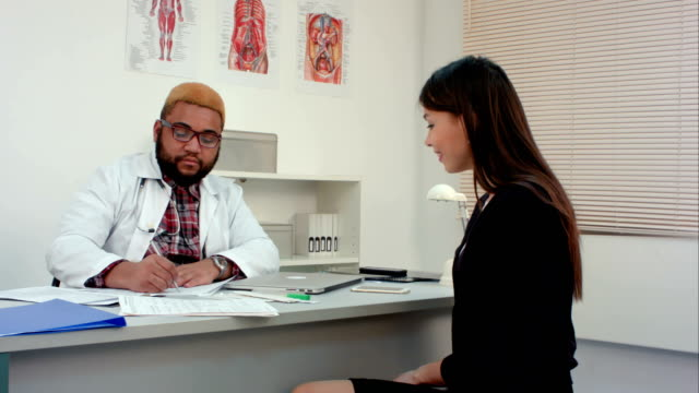 Male doctor talking to female patient and filling in medical form video