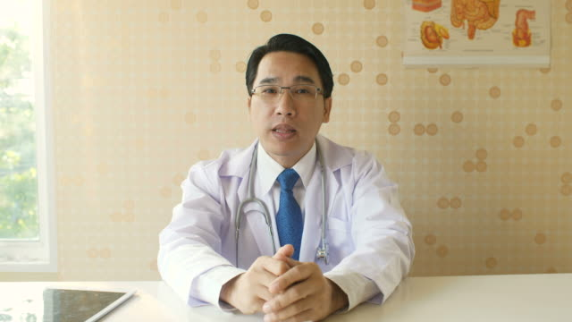 Male doctor talking with patient on a video call in his office video