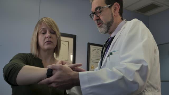 medico maschio che insegna a una paziente come utilizzare un'app per la salute dell'orologio intelligente - computer indossabile video stock e b–roll