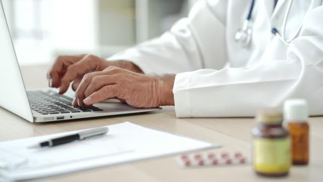 manliga läkare att skriva på dator - vårdklinik bildbanksvideor och videomaterial från bakom kulisserna