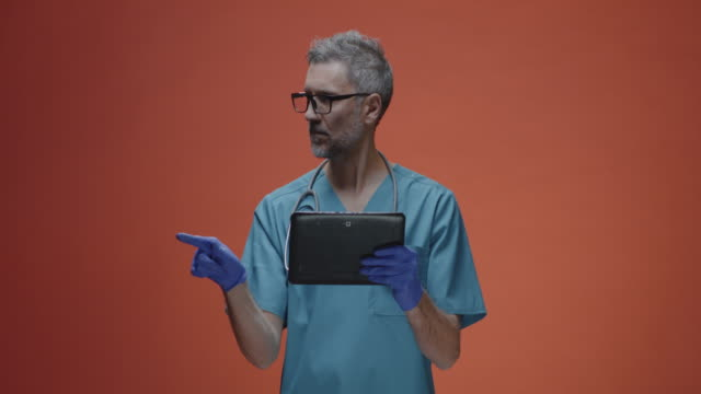 vídeos de stock e filmes b-roll de male doctor using a tablet - vr red background