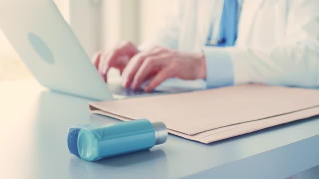 Male Doctor Using Laptop By Asthma Inhaler At Desk 4K video