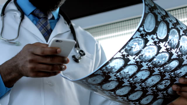 Male doctor viewing mri brain scan using smartphone video