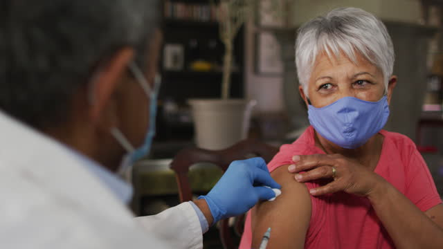 Male doctor visiting senior mixed race woman giving her vaccination Male doctor visiting senior mixed race woman giving her vaccination. both wearing face masks. self isolation retirement health care at home during coronavirus covid 19 pandemic. vaccine stock videos & royalty-free footage