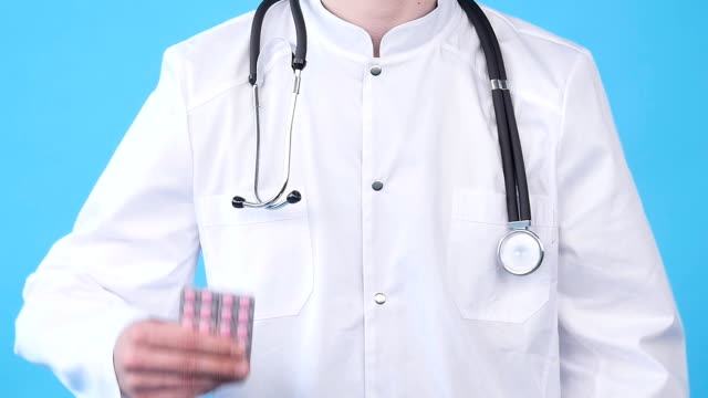 Male doctor with medicine in hands Male doctor with medicine in hands on a blue background painkiller stock videos & royalty-free footage