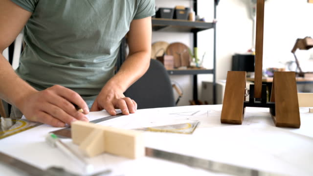 Male drawing and working on a wooden product in his studio. Anonymous footage. video