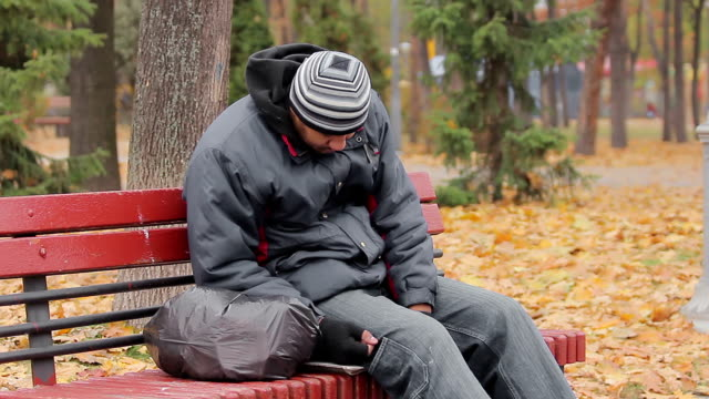 Male drinking addict sleeping on bench in autumn park, alcohol abuse problem