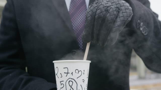 vídeos y material grabado en eventos de stock de hombre bebiendo café en la calle - moda de invierno