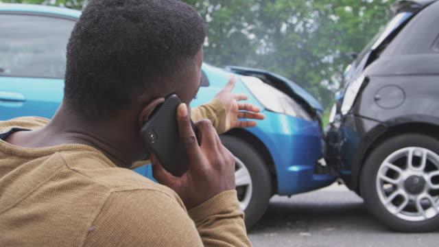 manlig förare inblandade i bilolycka ringer försäkringsbolag från vägkanten - bilolycka bildbanksvideor och videomaterial från bakom kulisserna