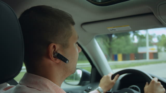 Male driver travelling by car on highway Closeup of confident male driver with hands-free device holding steering wheel with both hands while driving car on highway during business trip. Man travelling by car on freeway. hands free device stock videos & royalty-free footage