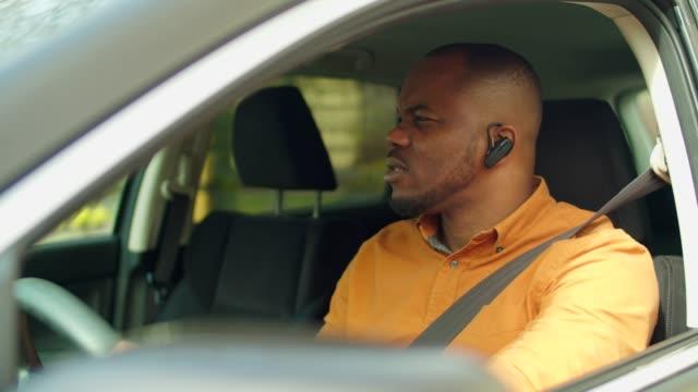 vídeos de stock, filmes e b-roll de motorista masculino usando fone de ouvido sem fio no carro - veículo terrestre