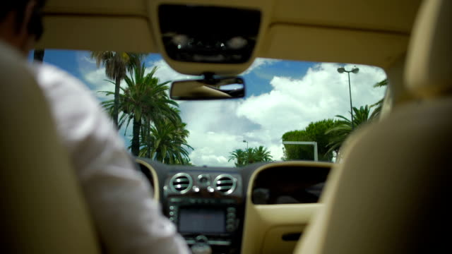 Male driving luxury vehicle in resort city, summer vacation, business trip video