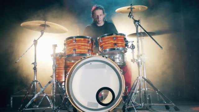 male drummer spelar trummor i rök. framsynthet av en man med dreadlocks spelar trummor - trumset bildbanksvideor och videomaterial från bakom kulisserna