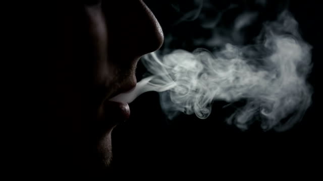 HD SLOW: Male during exhaling a cigarette smoke in slo-mo video