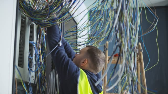 Male electrician connecting wires in a new electrical enclosure