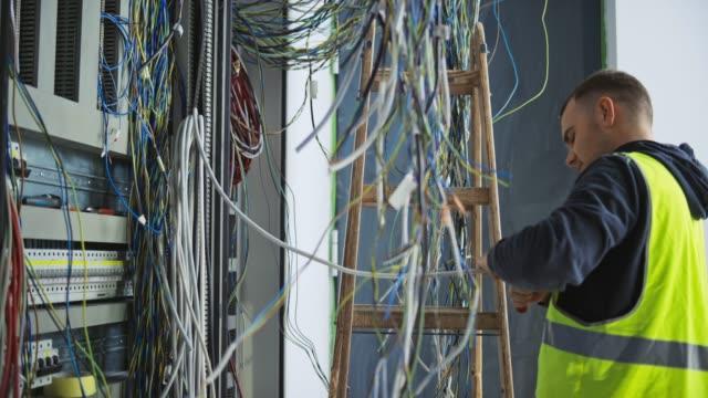 vídeos de stock, filmes e b-roll de eletricista masculino que instala cabos e fios em um cerco elétrico novo - eletricista