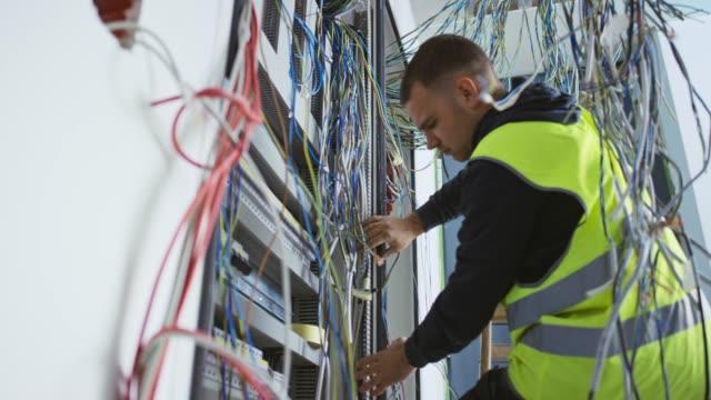 Electricista DS macho asegurándose de que todos los cables se colocan en su lugar en el gabinete de CA - vídeo