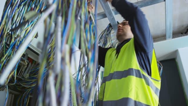 vídeos y material grabado en eventos de stock de electricista masculino organizando paquetes de cables antes de instalarlos en la carcasa de ca - cable
