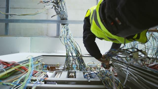 vídeos de stock, filmes e b-roll de ld eletricista masculino que trabalha em um cerco elétrico novo que descasca fios e que prepara os para a instalação - eletricista