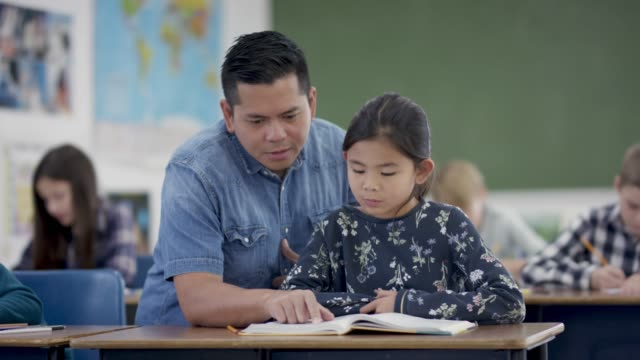 Male Elementary school teacher working with his students A smiling elementary school teacher helps his students with their work in the classroom. middle school teacher stock videos & royalty-free footage