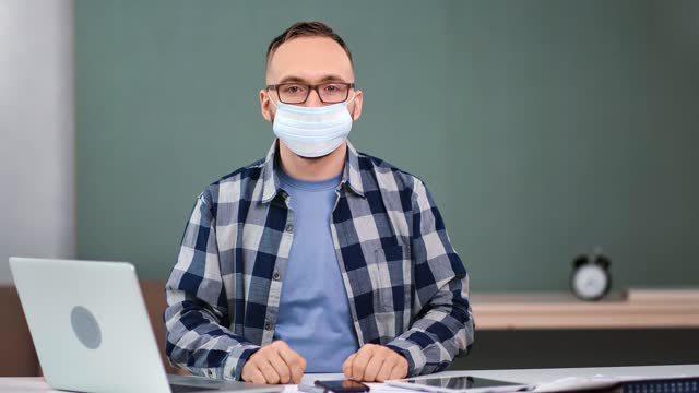 Male employee putting on medical face mask posing sitting at table. 4k Dragon RED camera