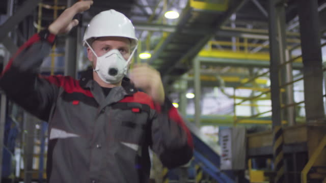 male engineer in hardhat and respirator walking along production line - mask стоковые видео и кадры b-roll